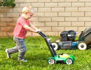 Kind met speelgoed grasmaaier